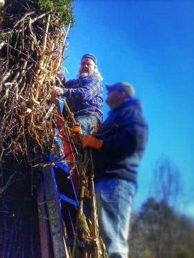 Nels Linde and a volunteer add corn stalks to the Corn King