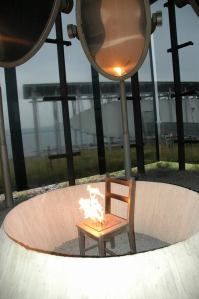 Hanging high above the chair are oval brass mirrors that reflect the light. That's all there is to this memorial, but, in my opinion, no more words are needed. I found it to be a chilling and yet holy place. When I showed this photo to my cousin Kristin Skoglund and her husband, he got it right away. ``The flames are the spirits of those who were killed, rising up away from this place,'' he said. — at Steilneset Memorial in Vardø, Norway.